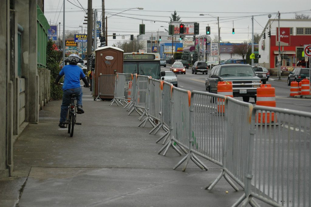 Photo of sidewalk divided from a busy street full of cars and traffic cones
